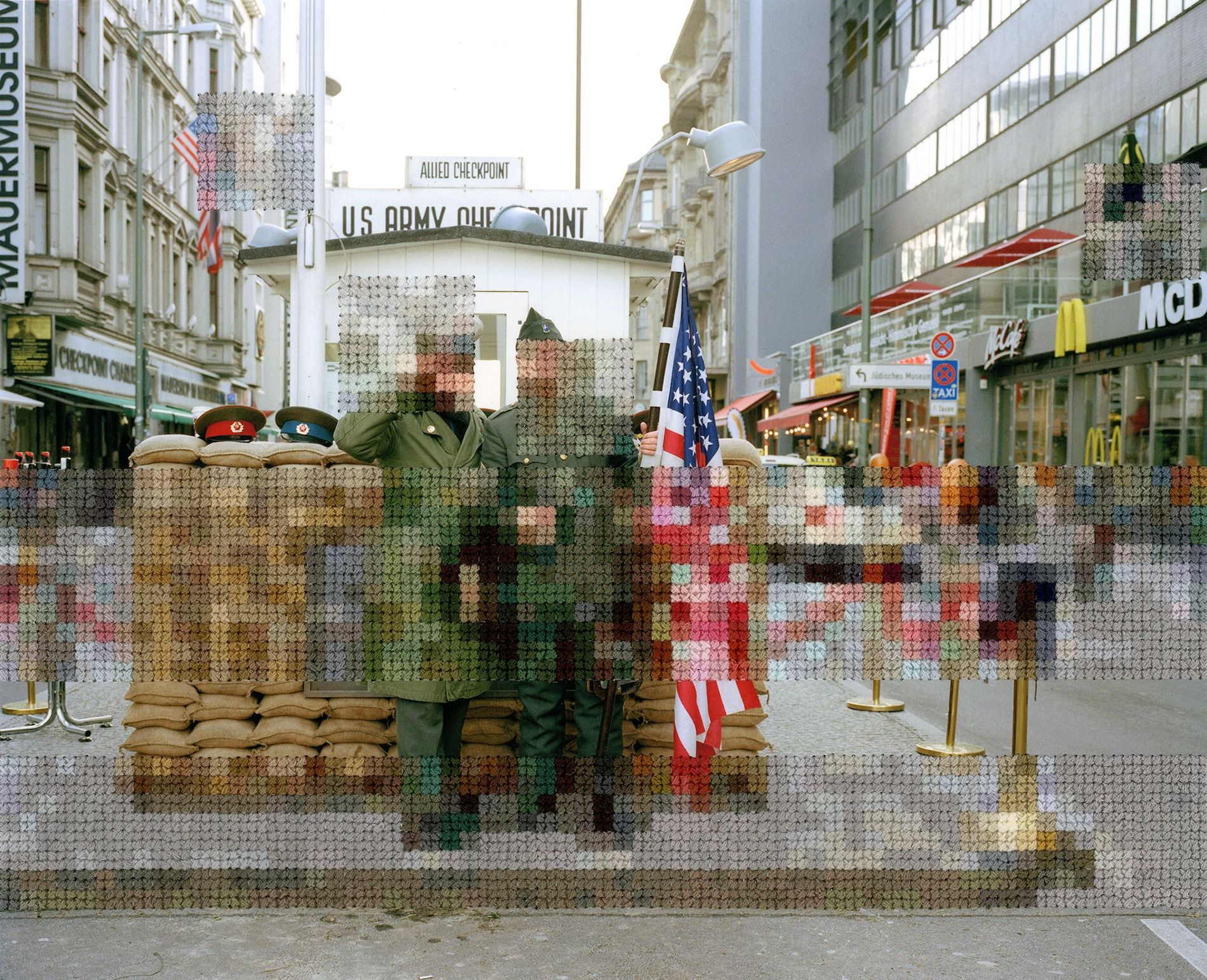Color photo of Berlin military checkpoint with embroidery resembling pixels stitched into parts of the image