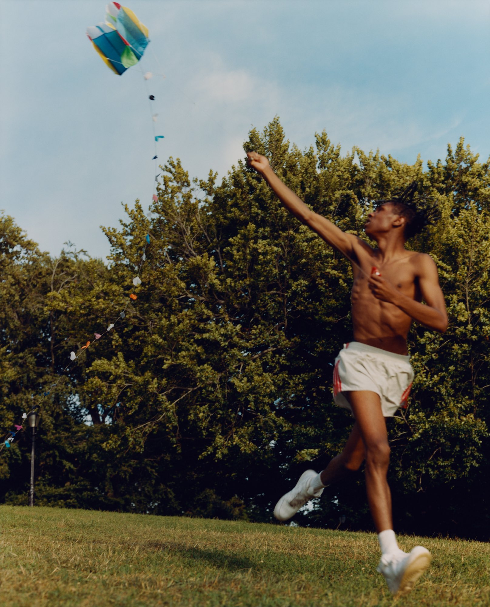 Color photo of an adolescent boy mid-leap with a kite in a field