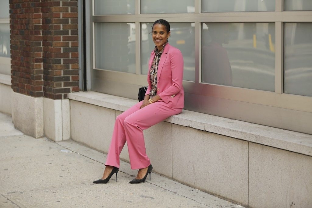 A woman in a pink suit seated on a window sill.