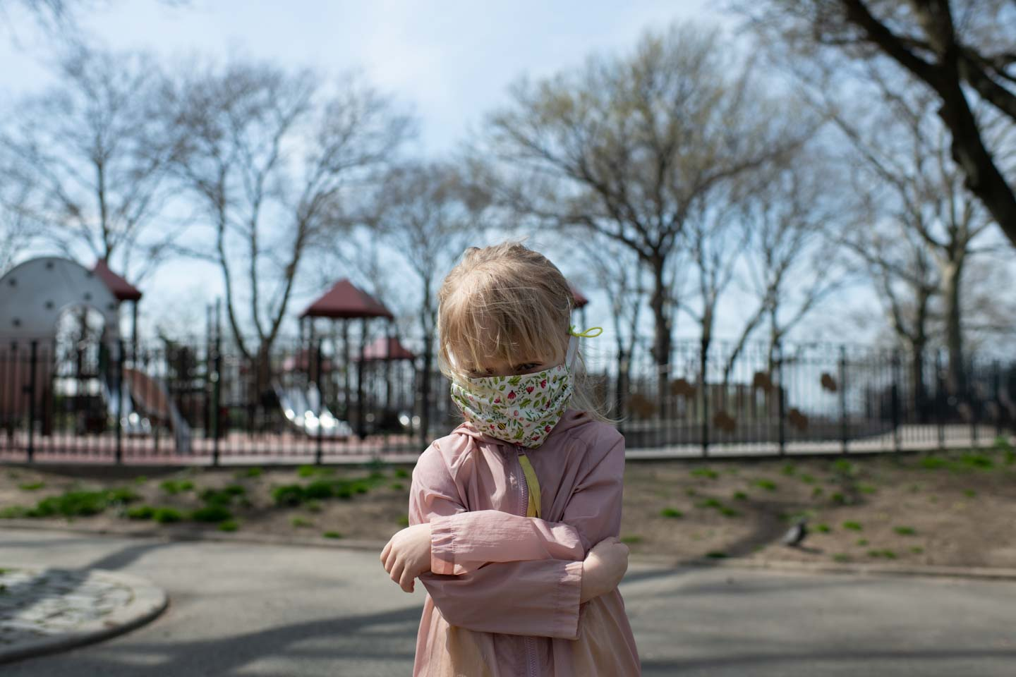 A little girl with a face mask on crosses her arms in front of gated playground