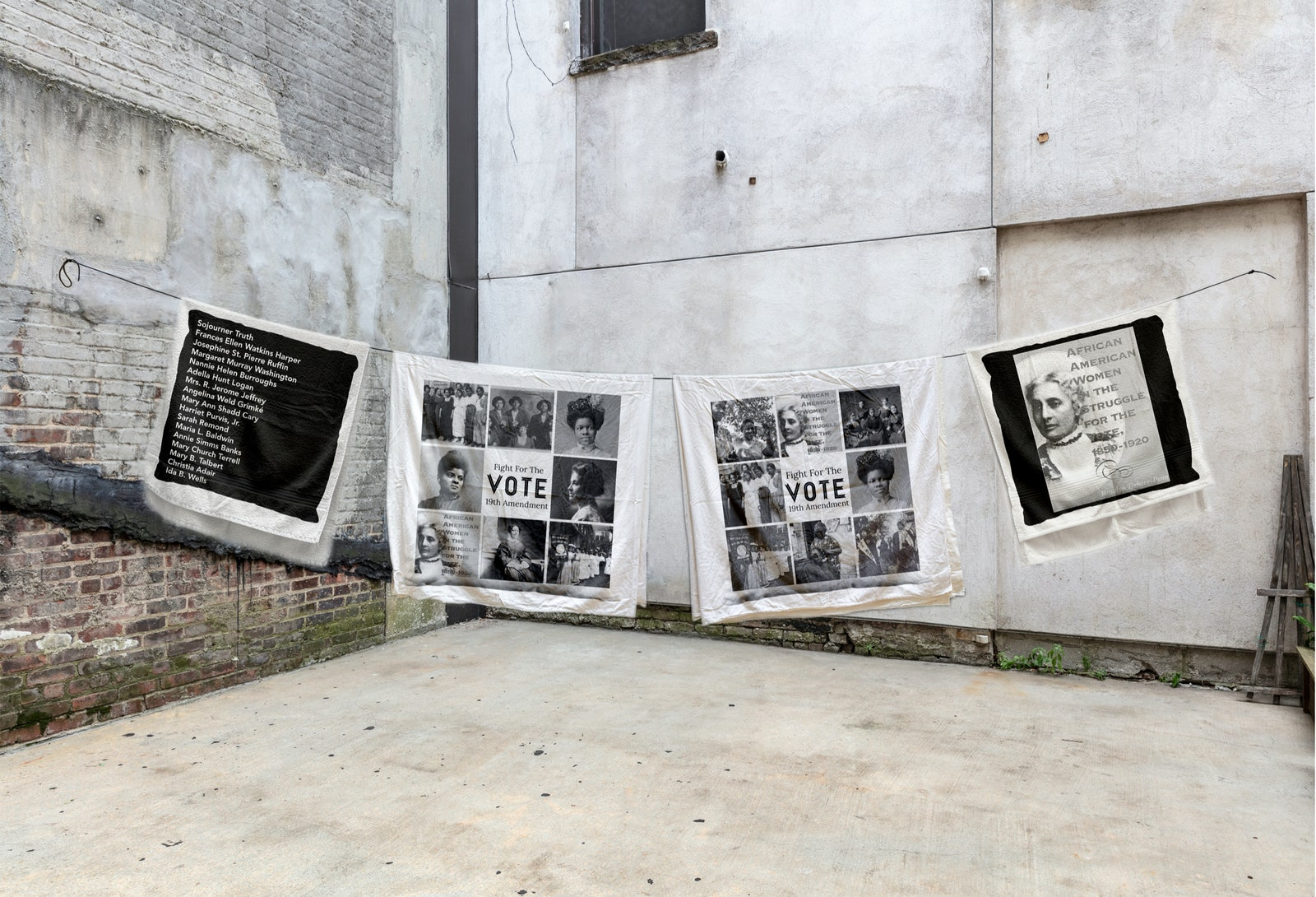A clothing line strung across a concrete yard with black and white photos of the suffragette movement attached.