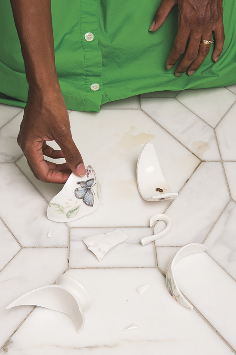 A close up of a black woman's hands picking up a broken teacup off a tiled floor
