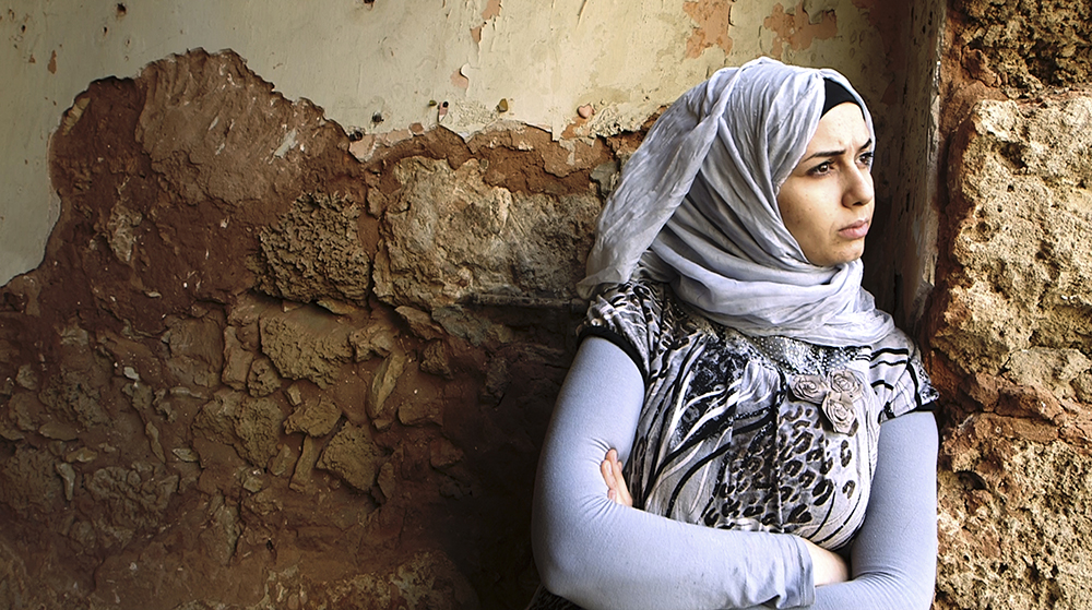 Woman in hijab against stone wall