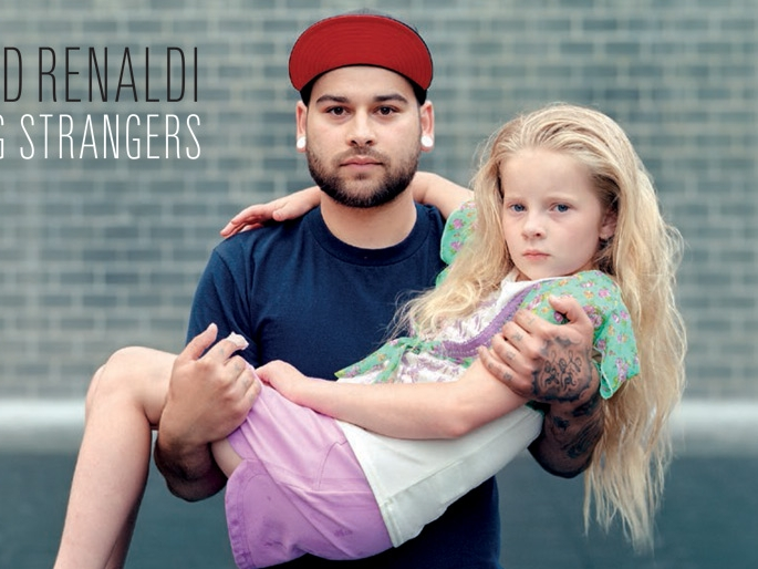 A photo by Richard Renaldi depicting two strangers; An adult male holding a young girl in his arms.