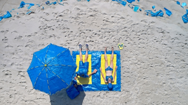 Photograph of a couple sunbathing using towels, beach umbrella, bathing suits and other items made of IKEA plastic bags.