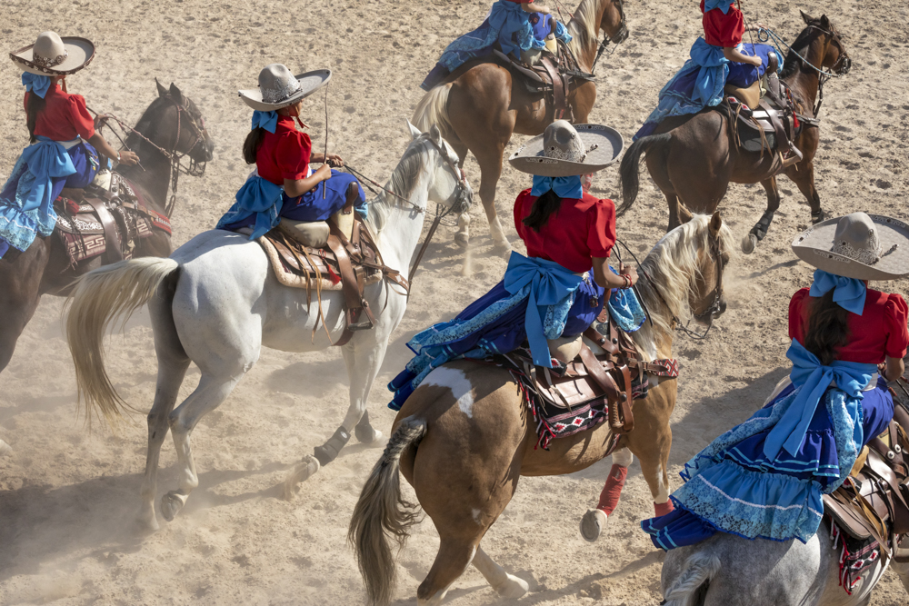 Women on horseback perform the Escaramuza in the arena