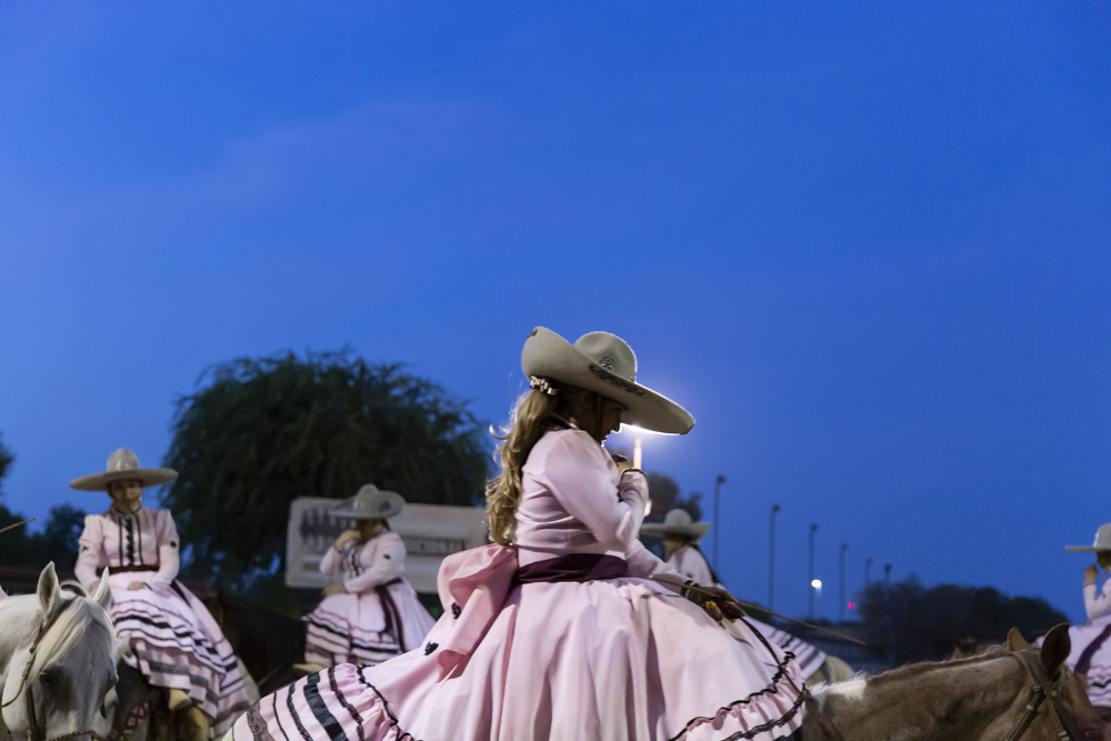 performers in arena perform a prayer on horseback