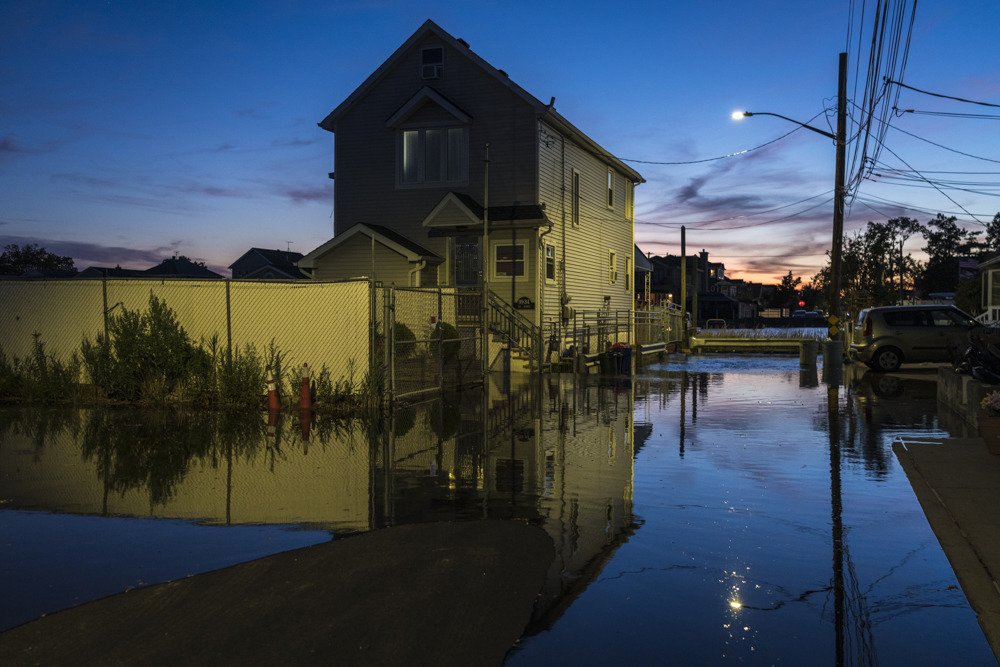 color photo of a home on waterfront flooded due to global warming