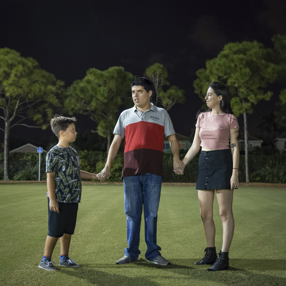 portrait of a family standing in a field, next to a letter addressed to a sibling of a person with autism
