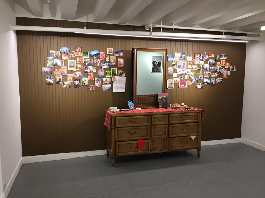 Installation view of Tiger Balm. A bureau and mirror with various photographs stuck to a wood paneled wall.