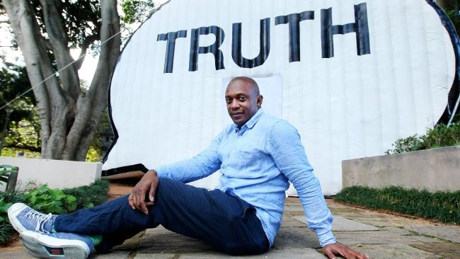 willis thomas poses in front of inflatable truth booth