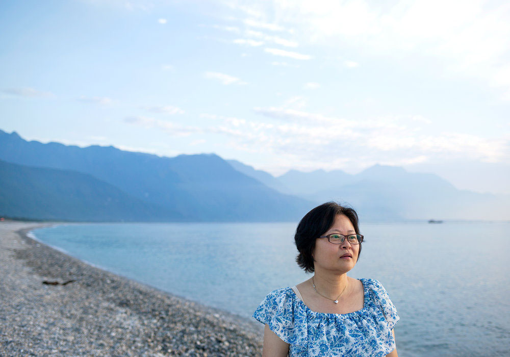 A woman stares into the distance with a dramatic seascape and mountains behind her