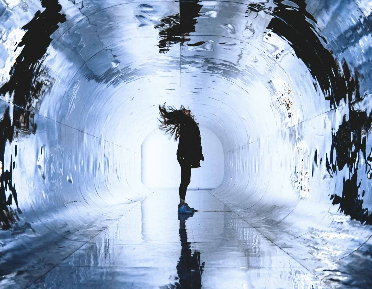 person in reflective tunnel