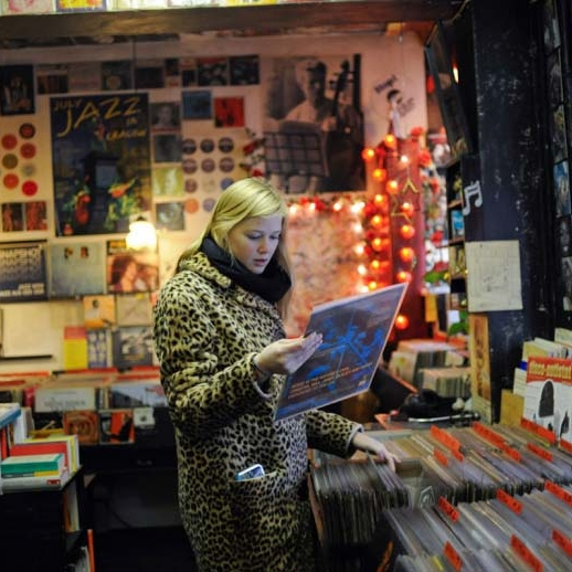 Female student browsing in a record shop, holding a vinyl record.