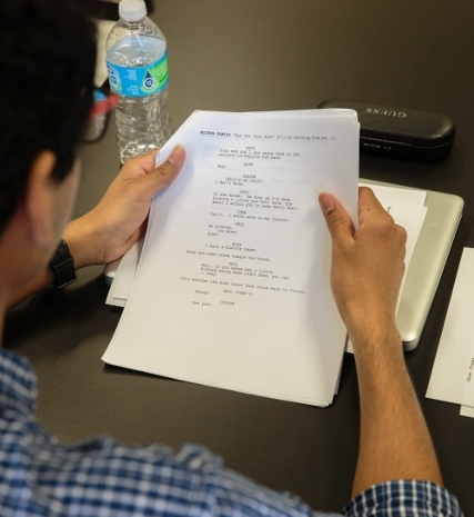 Over the shoulder shot of a student holding an open script