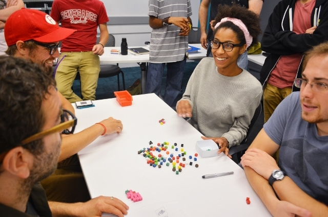 Four students at a table with tokens playing or creating a game.