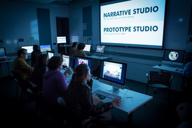 Students in class, watching a Powerpoint presentation on Narrative Studio and Prototype Studio.