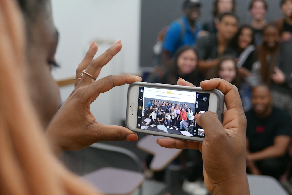 Student taking a group photo with her phone.