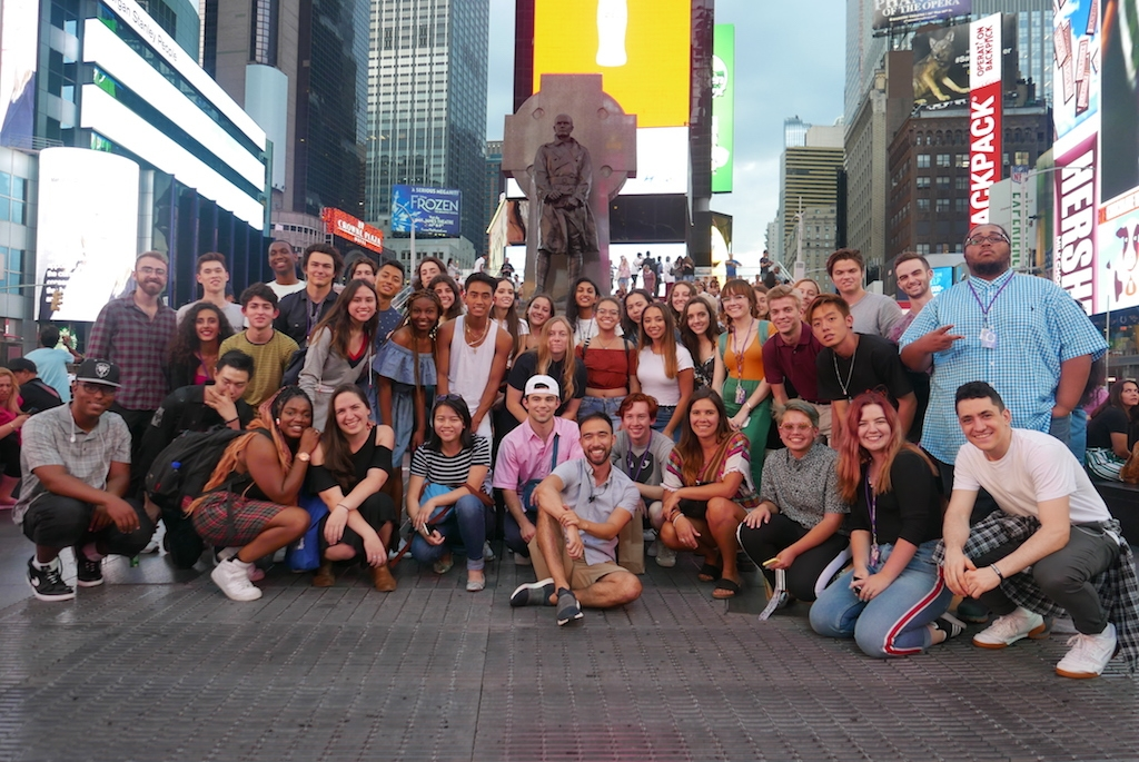 Group photo of students in Times Square at night
