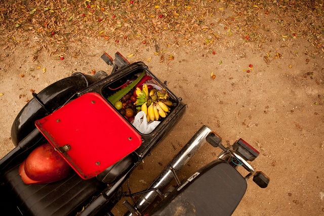 Trunk on a motorbike with fresh fruit and vegetables.
