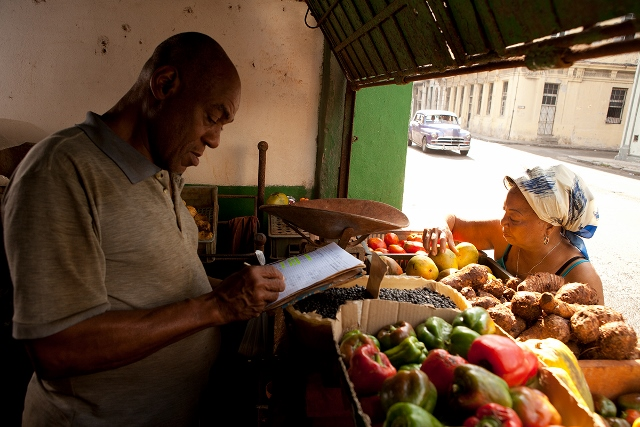 Man selling fruit and vegetables at a produce stand.