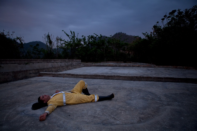 Man lying on the ground with arms outstretched in an open concrete plaza near a field.