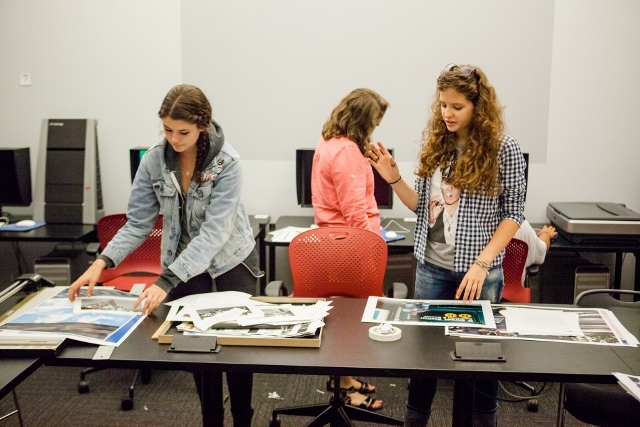 Three female students preparing and editing photos on a long table.
