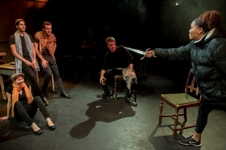 Actors presenting Henry IV. One actor has a sword drawn and is threatening the other performers on stage.