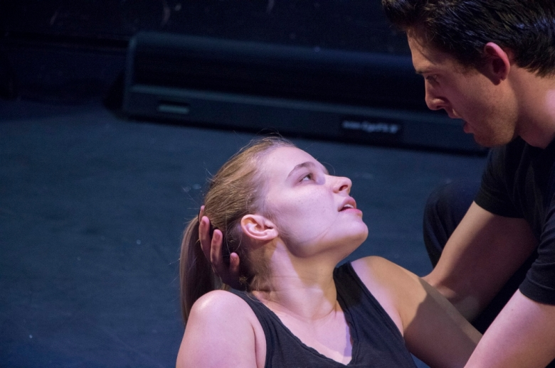 Female actor lying on the floor, head cradled by a male actor.
