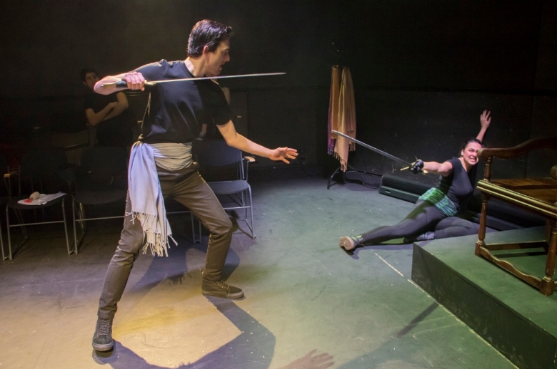 Two actors in combat, with swords, one cornered and on the floor.