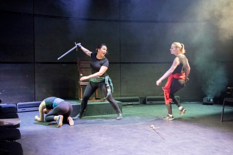 Two actors in stage combat, one using a sword to attack the other.
