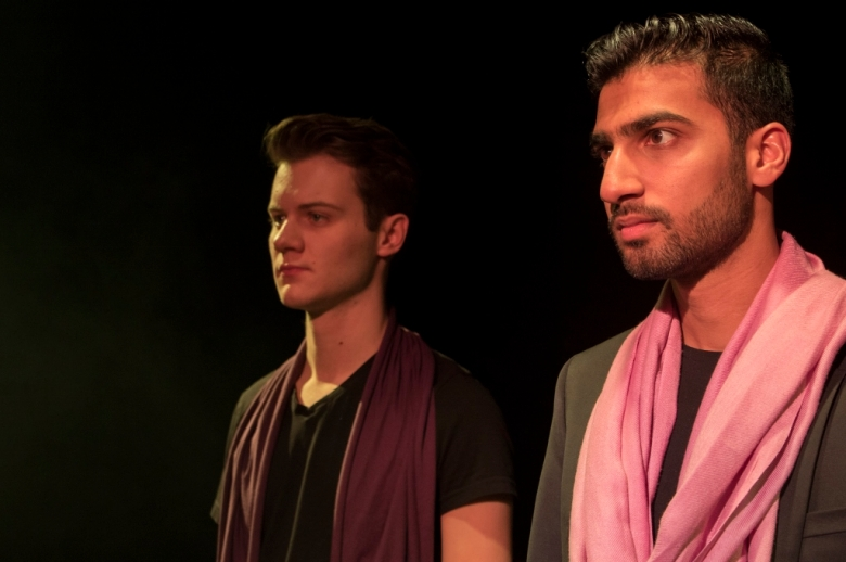 Two male actors standing on stage, one wearing a maroon scarf, the other wearing a pink scarf.