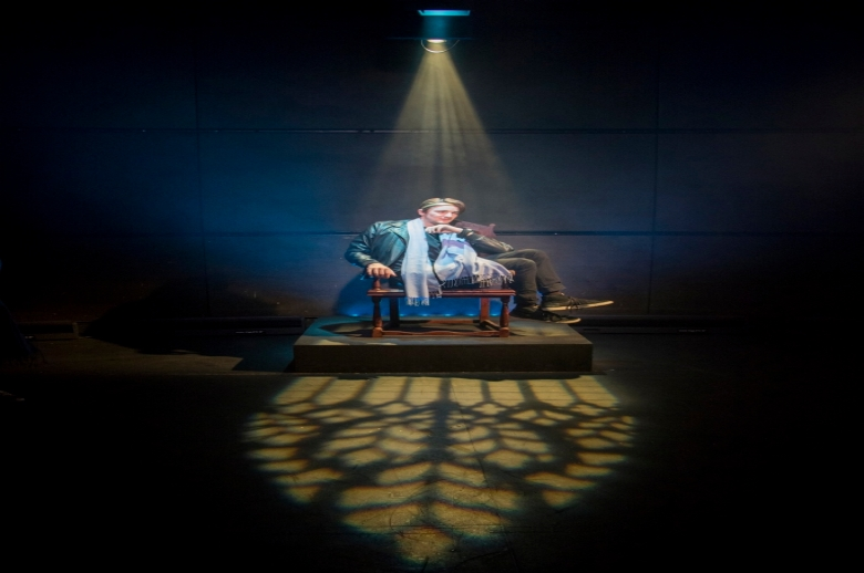 Actor seated on a throne, under a single spotlight.
