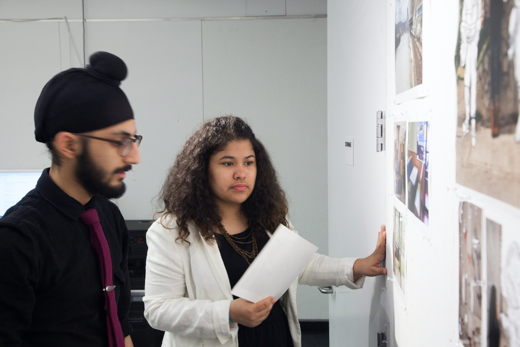 Students displaying photos on a wall