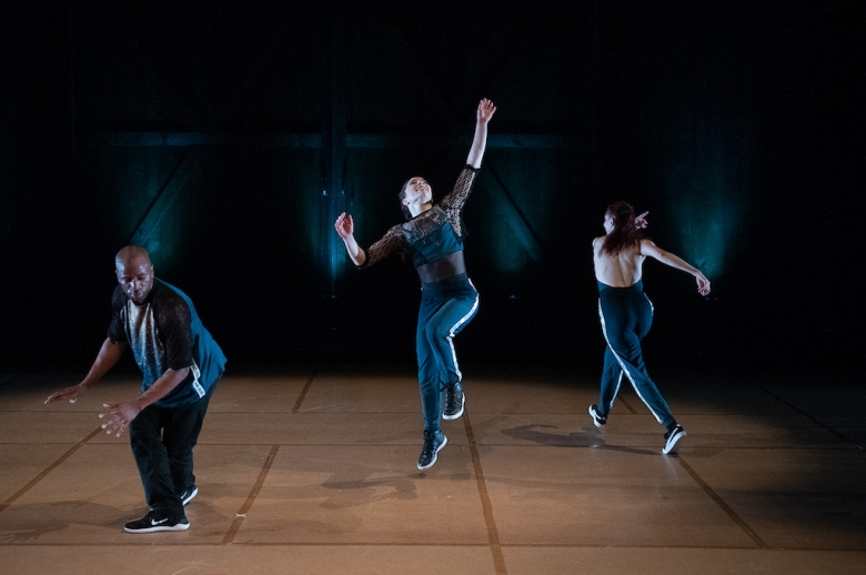 Three dancers in mid-performance