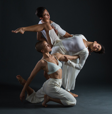 Three dancers posing, bodies interlocked.