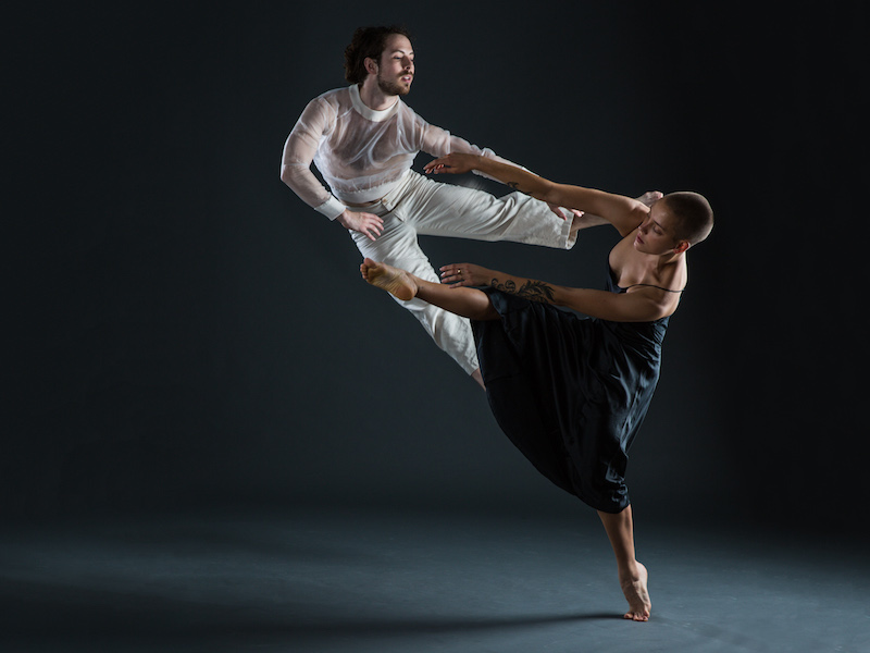 Dancers in mid-duet. Woman en pointe, lifting her male partner.