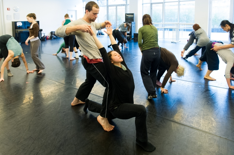 Studio class with dancers paired in various positions.
