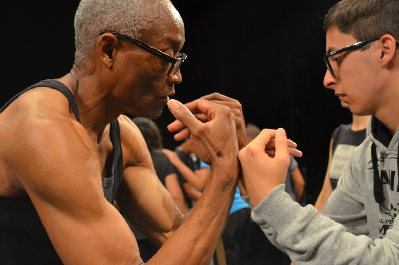 Two performers, one older and one younger, with their fists raised face to face in a dance training exercise