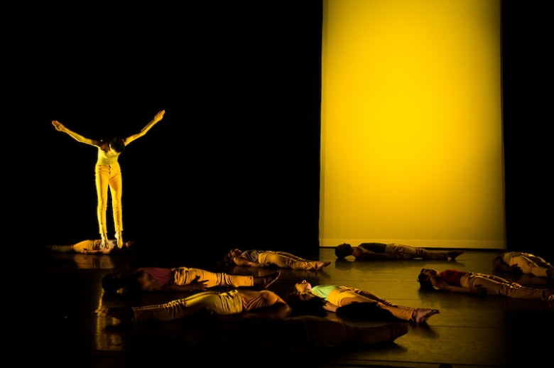 Dancers lying on stage, backlit by yellow light, with one solo dancer standing with arms raised.