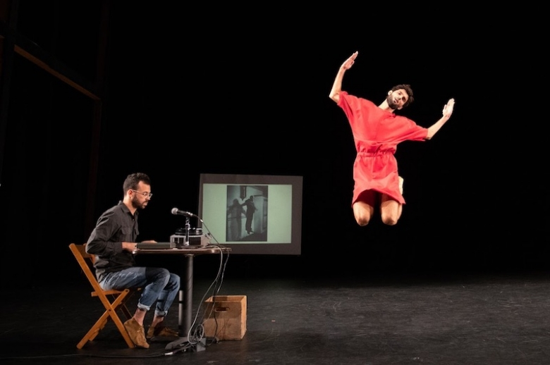 Two performers on stage, one jumping in midair, with the other seated running a film projector