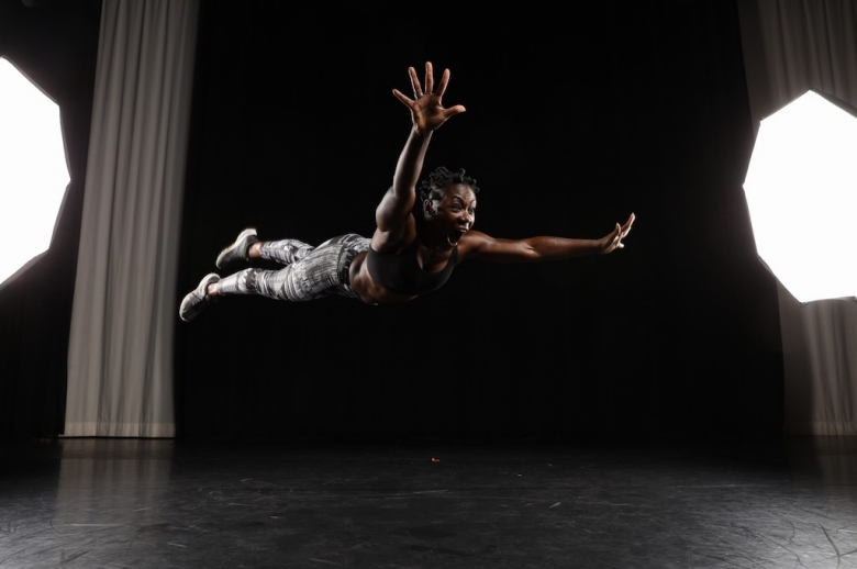 Dancer flying forward, hands stretched out, on stage