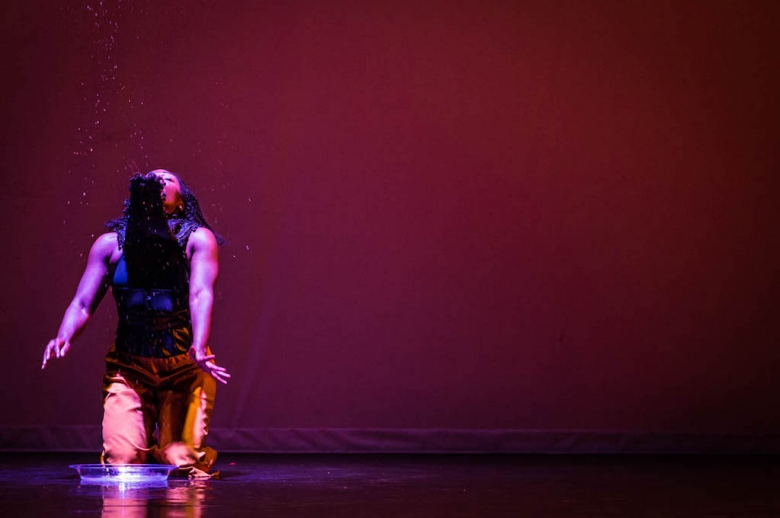 Dancer kneeling on stage, with back to audience and arms reaching behind her