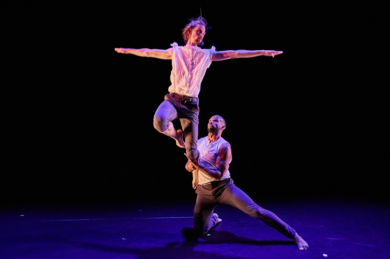 Two dancers on stage, one lifting the other one