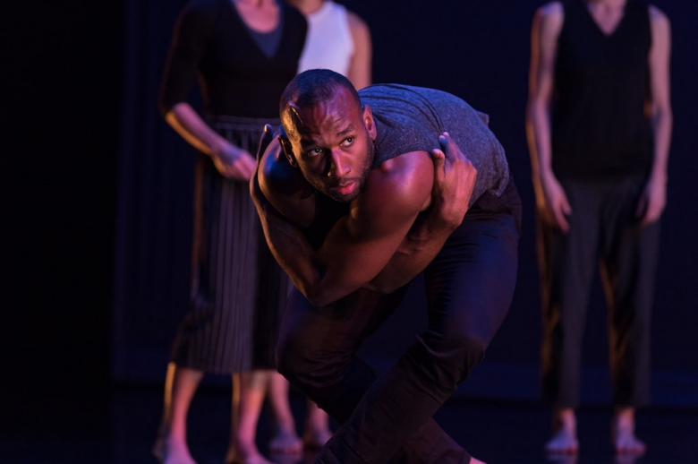Male dancer grabbing his arms and leaning forward, looking at the camera