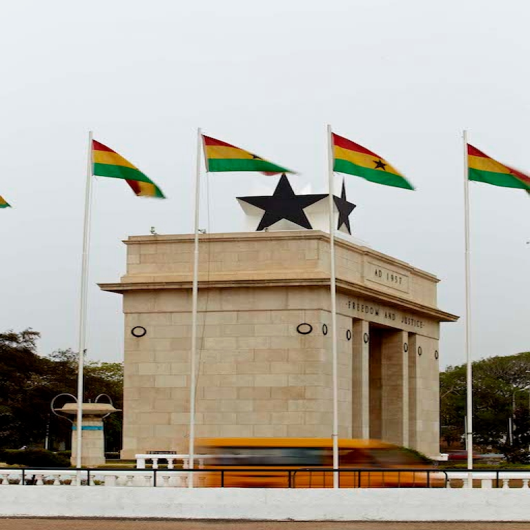 Ghanian flags waving on top of the Freedom and Justice Arch