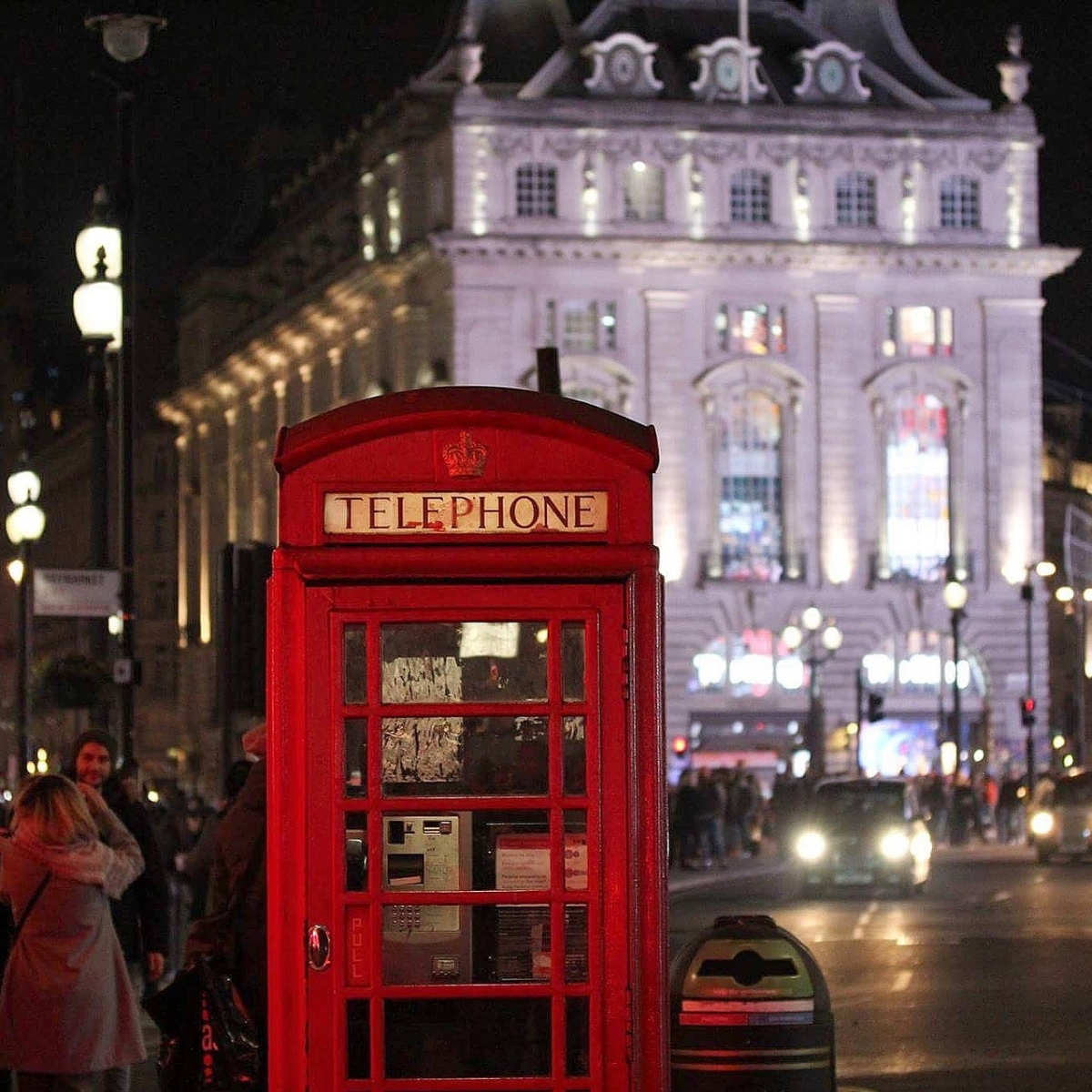 Red telephone box in London at night