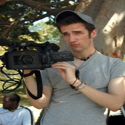 Male student holding a video camera
