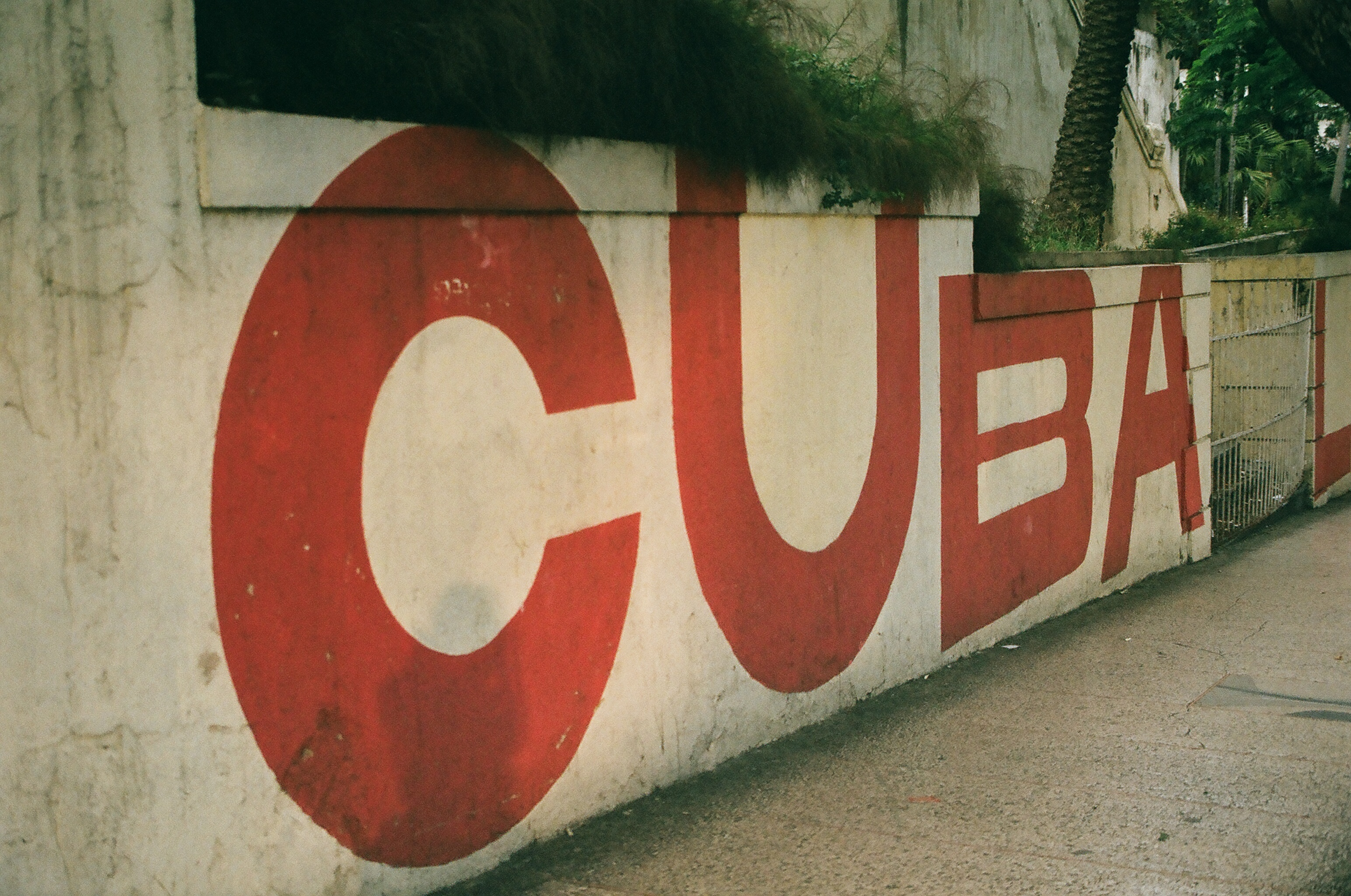 "The word ""Cuba"" painted in red block letters on a wall in Havana."