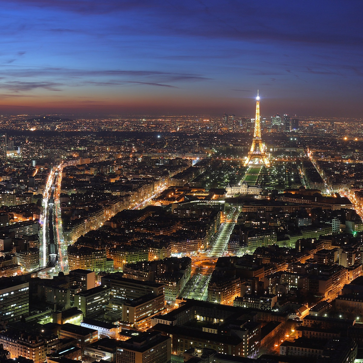 Paris skyline at night, including the Eiffel Tower.